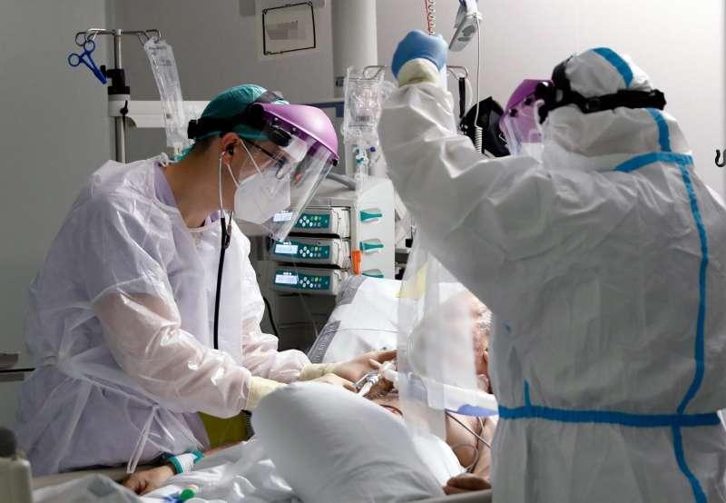 Personal sanitario atienden a un paciente en la Unidad de Cuidados Intensivos.