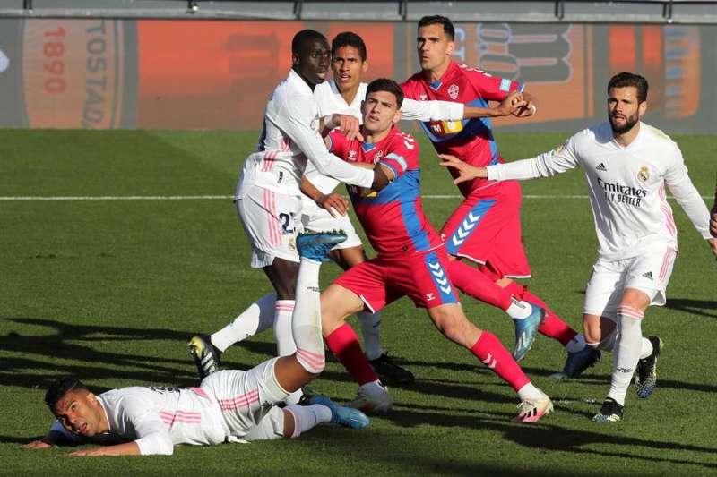 El jugador del Elche Dani Calvo (c), se prepara para rematar a gol ante la oposición del jugador del Rea Madrid Rodrygo. EFE/ Kiko Huesca