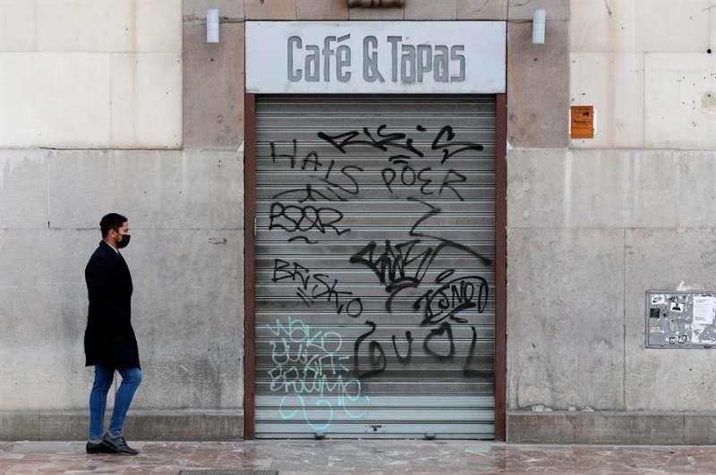 Una persona pasa ante una cafetería cerrada en el centro de València.EFE/Kai Försterling