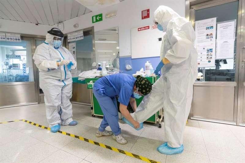 Sanitarios se protegen con trajes de protección personal antes de entrar en un box para atender a un paciente ingresado por coronavirus. EFE