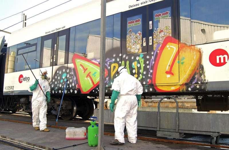Fotografía facilitada por Ferrocarrils de la Generalitat Valenciana de la limpieza de los grafitis pintados en vagones. EFE/Archivo