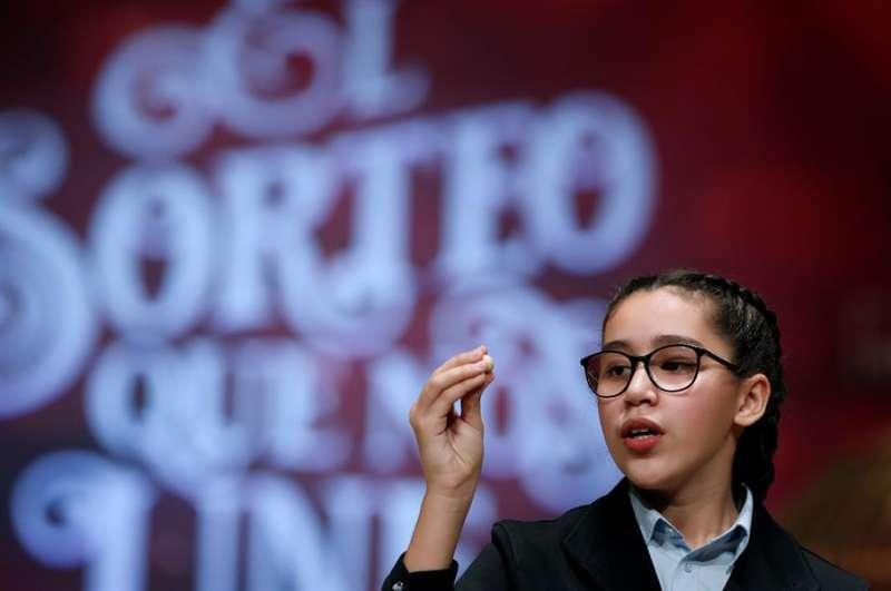 Noura Akrouh canta el número 38341, agraciado con un cuarto premio del Sorteo Extraordinario de la Lotería de Navidad. EFE/J.J. Guillén