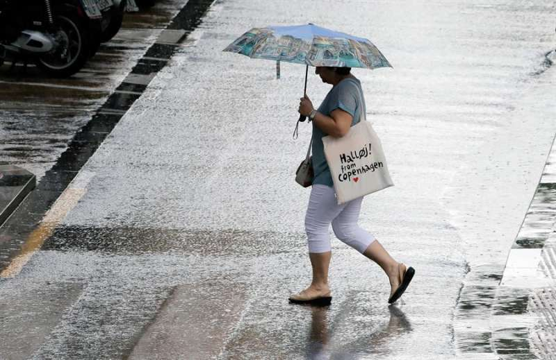 Una mujer camina con un paraguas bajo la lluvia. EPDA/Archivo