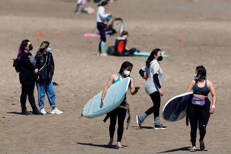 Imagen de archivo de un grupo de jóvenes en la playa de la Malvarrosa llevando mascarillas. EPDA