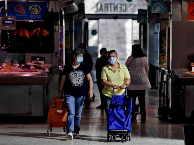 Dos mujeres realizan sus compras con mascarilla. EFE