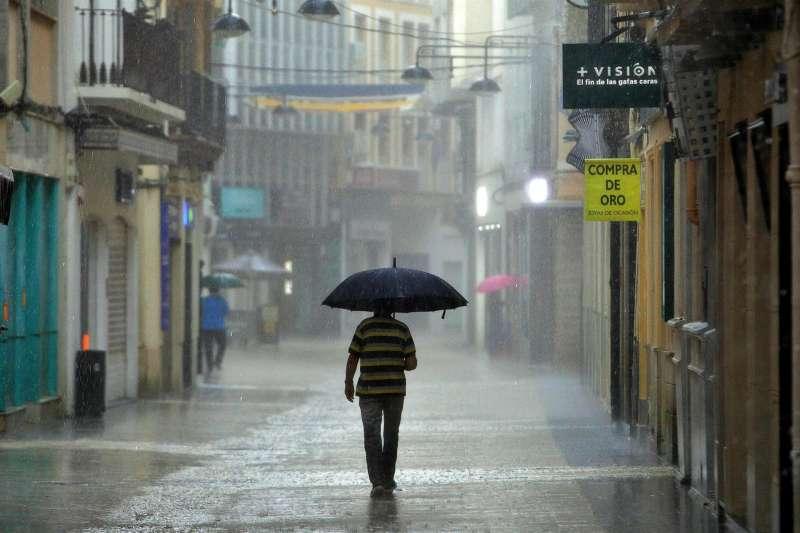 Un hombre camina bajo una intensa lluvia.