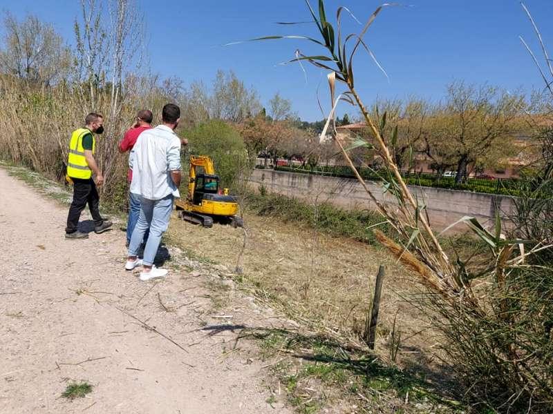 La maquina trabajando en la ribera del río