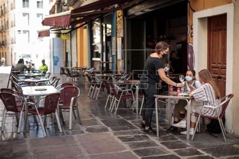Una camarera atiende una mesa de una terraza en el centro de València.