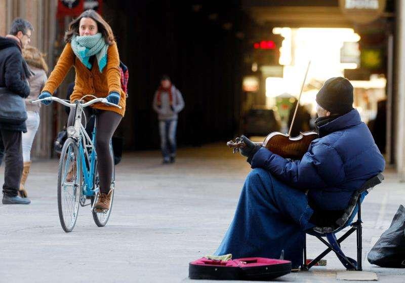 Un músico callejero se refugia del frío con una manta en las piernas y guantes en un céntrico pasaje de València. EFE/Archivo