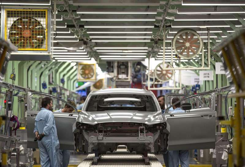 Varios trabajadores de la planta de pintura de Ford en Almussafes, revisan una carrocería tras su paso por la zona de pintura.