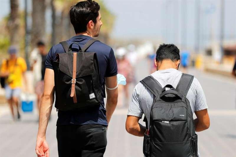 Dos jóvenes caminan por el paseo marítimo de Valencia. EFE/Manuel Bruque/Archivo