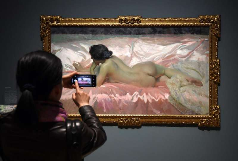 Imagen de archivo de una visitante tomando una foto de la obra
