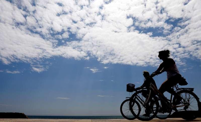 Dos personas pasean en bicicleta por la playa.