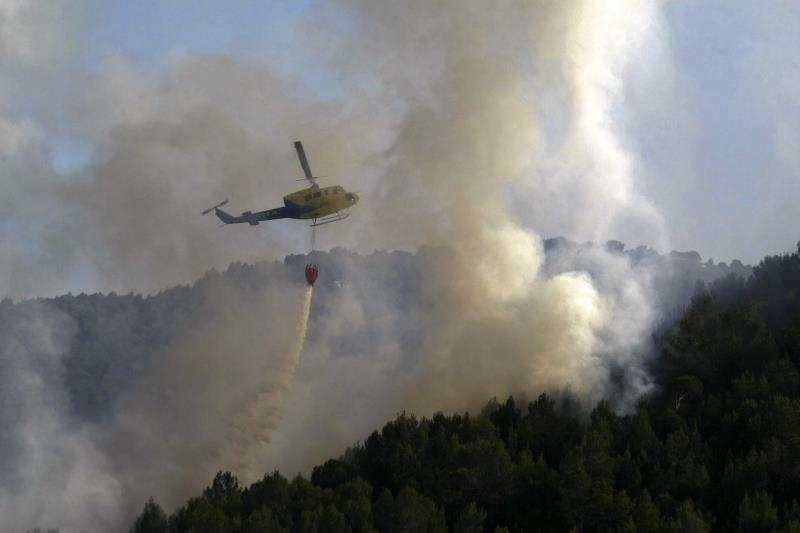 Fiscal exculpa a 3 procesados por el incendio con 2 muertos en Torremanzanas. Un helicóptero lanza agua sobre la zona forestal incendiada cerca de la población de Torremanzanas. EFE/Archivo