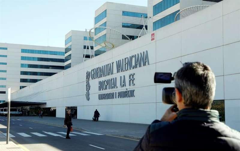 Un periodista toma imágenes del exterior del hospital La Fe. EFE