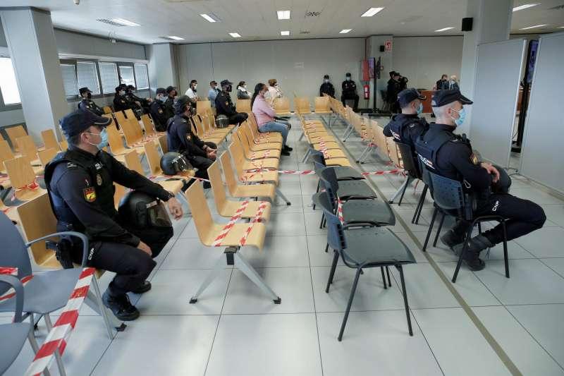 En la imagen, varios de los acusados, rodeados de policías, en la sala del juicio.