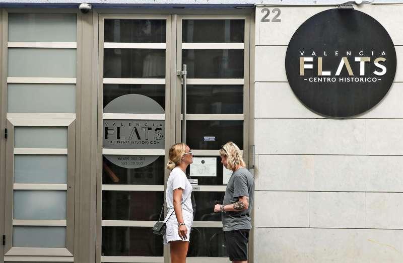 Una pareja de turistas se dispone a entrar en edificio de apartamentos situado en el Barrio del Carmen de València.