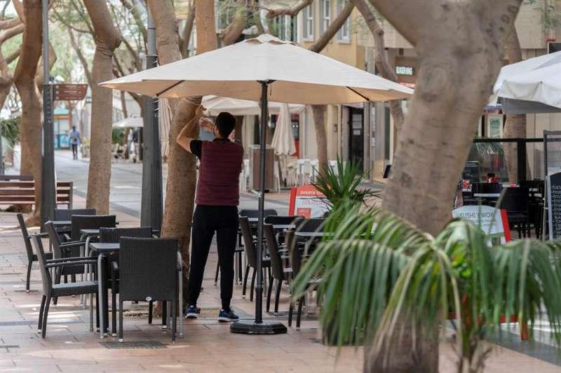 Un camarero coloca una sombrilla una terraza de un bar. EFE/Archivo