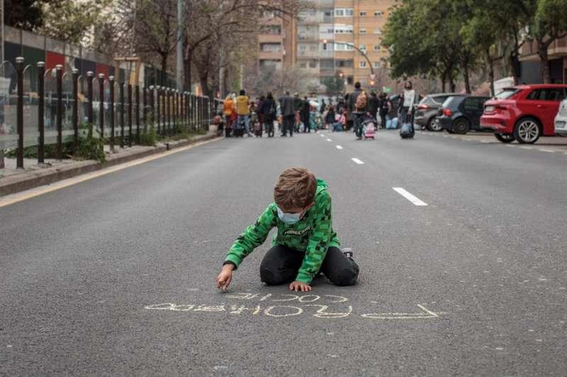 Un niño escribe con tiza en el asfalto ?prohibido coches? durante la protesta. EFE/Biel Aliño