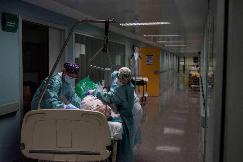 Sanitarios atienden a un paciente recuperado de coronavirus en el pasillo de la unidad de vigilancia postquirúrgica. EFE/ Brais Lorenzo/Archivo