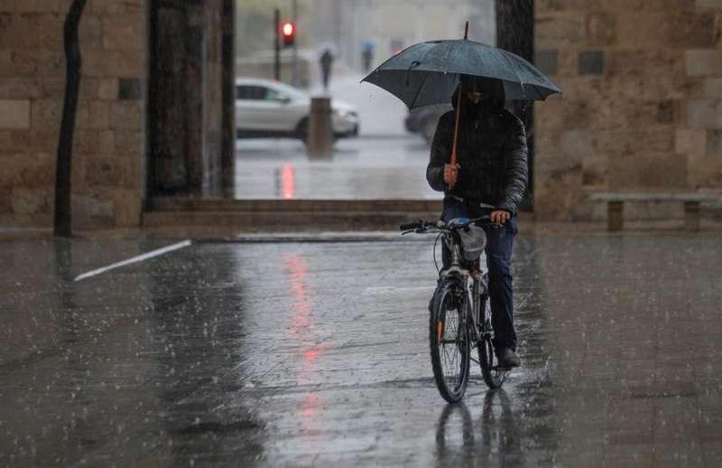 Una persona circula con su bicicleta por la calle mientras llueve. EPDA/Archivo