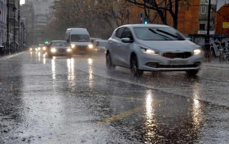 Varios vehículos circulan bajo una intensa lluvia este viernes en la ciudad de València. EFE
