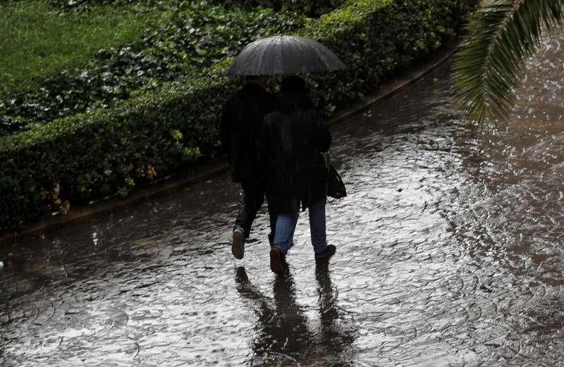 Dos personas se protegen bajo un paraguas de la intensa lluvia en una imagen de archivo.
