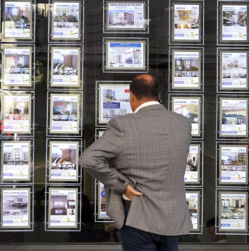 Una persona observa un escaparate de una inmobiliaria en Bilbao. EFE