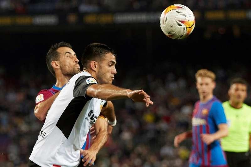 El delantero uruguayo del Valencia, Maxi Gómez, disputa el balón ante el centrocampista del FC Barcelona, Sergio Busquets.
