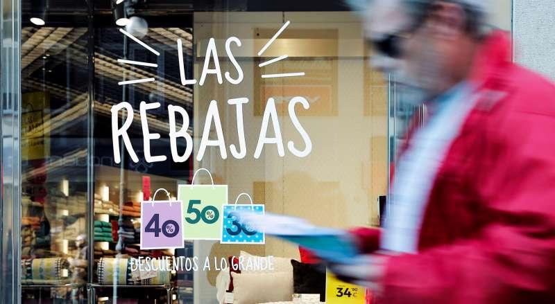 Un hombre pasa ante el escaparate de una tienda que ofrece descuentos de hasta el 50%. EFE/Archivo Manuel Bruque