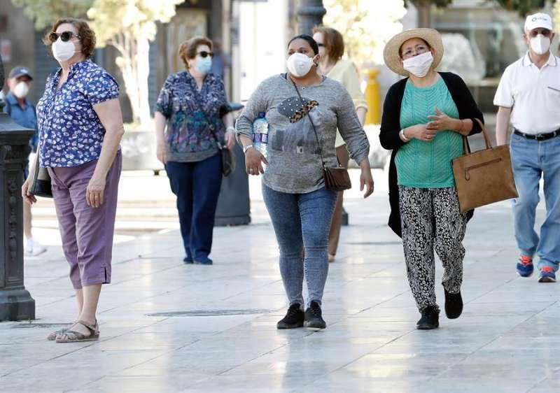 Varias personas caminan con mascarilla estos días. EFE