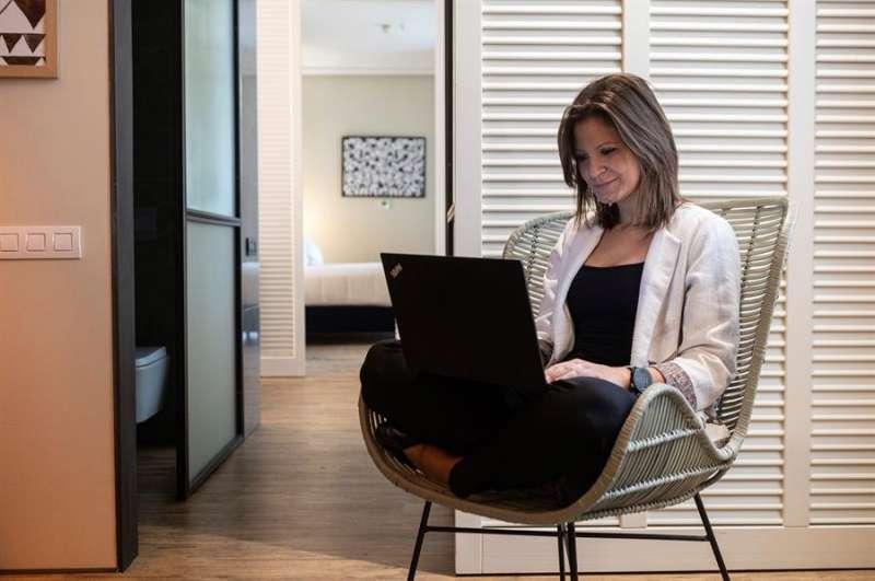 Una mujer trabaja en una habitación de un hotel que ofrece habitaciones para teletrabajar. EFE/Archivo
