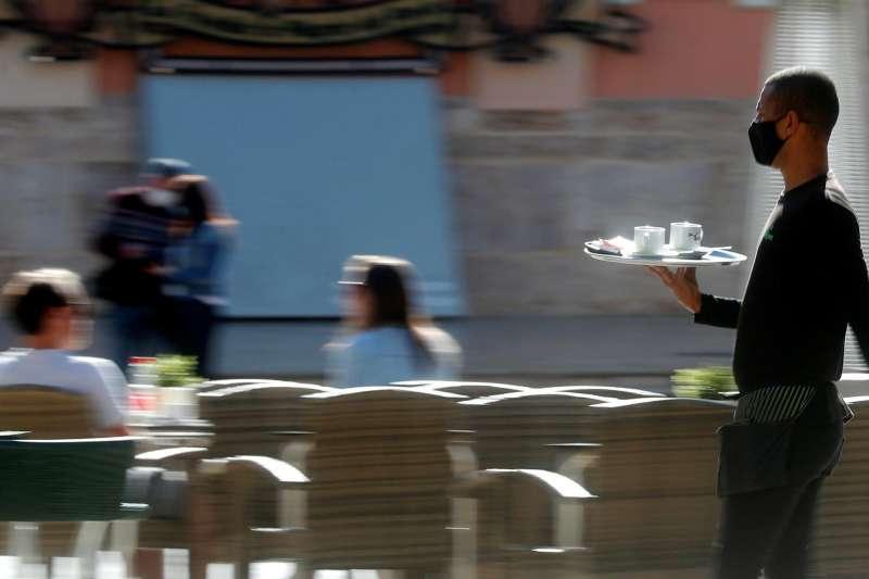 Un camarero sirve una mesa en el centro de València.