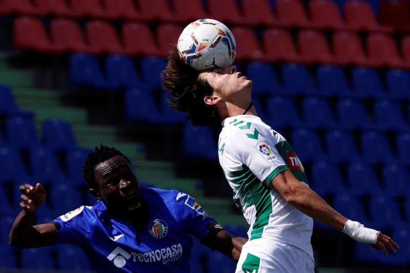 El centrocampista del Elche Pere Milla remata de cabeza ante el defensa togolés del Getafe Djené Dakonam. EFE