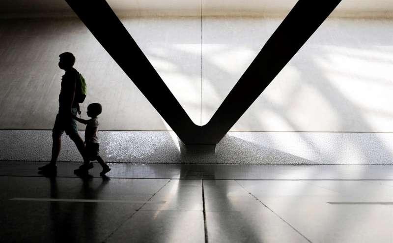 Un padre y su hijo caminan de la mano.
