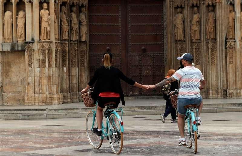 Una pareja recorre la plaza de la Virgen de Valencia.