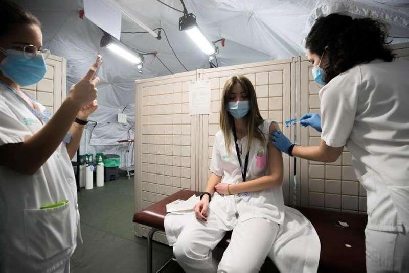 Sanitarios vacunan a una compañera. EFE/Javier Cebollada/Archivo.