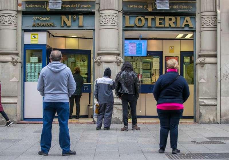 Un grupo de personas hace cola para comprar lotería en una administración. EFE/Archivo
