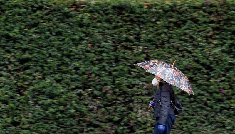 Una mujer se protege con un paraguas de la lluvia.