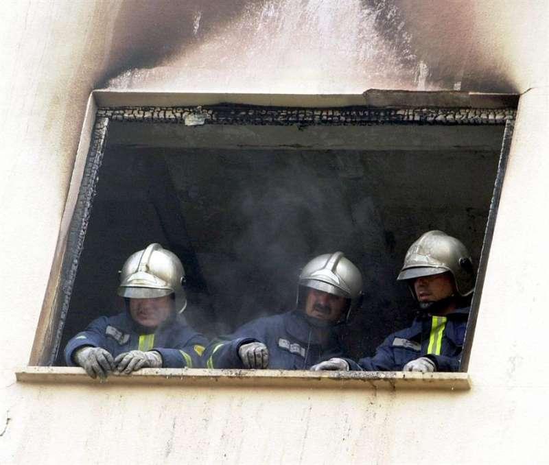 Tres bomberos desescombran una de las ventanas de una vivienda EFE/J.C.CARDENAS/Archivo