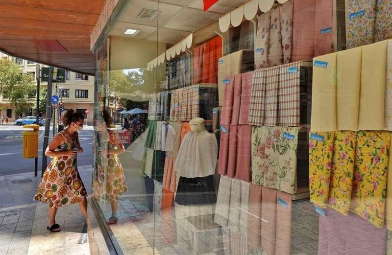 Una mujer con mascarilla entra en una tienda de tejidos. EFE/Manuel Bruque/Archivo