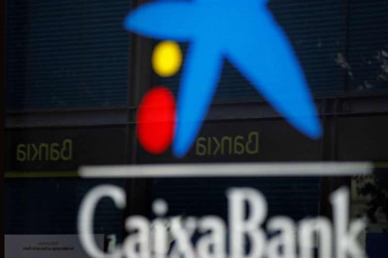 Vista de una oficina de CaixaBank y otra de Bankia reflejada en el cristal. EFE