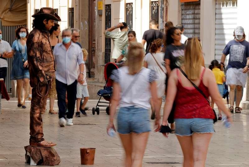 Un artista callejero espera una moneda de los turista este domingo en la calle Miguelete de Valéncia, en el centro histórico de la ciudad. Arhivo/EFE/Manuel Bruque