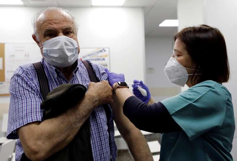 Una sanitaria vacuna a una persona mayor en un ambulatorio de València. EFE/ Juan Carlos Cárdenas/Archivo