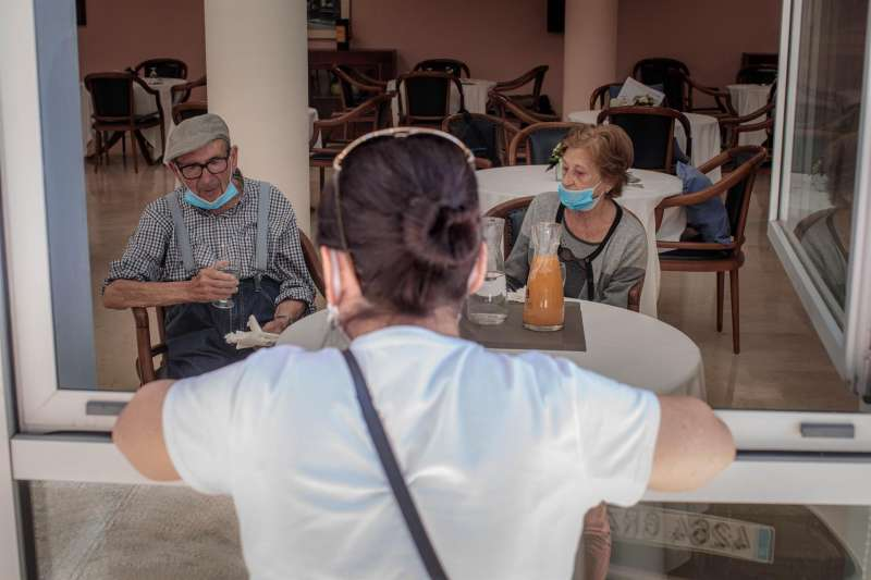 Una persona conversa con sus padres a través de una ventana habilitada en una residencia de  Valencia.