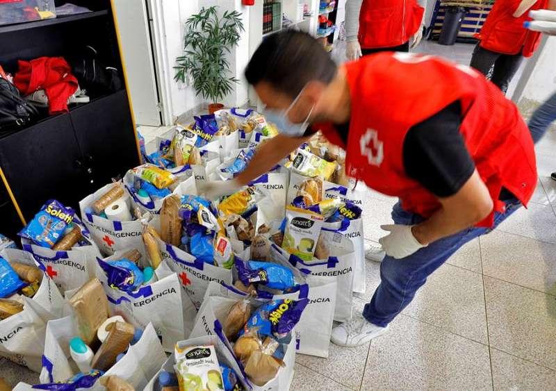 Un voluntario de Cruz Roja prepara las bolsas con productos de primera necesidad para repartir entre las personas con dificultades en Paiporta. EFE / Manuel Bruque