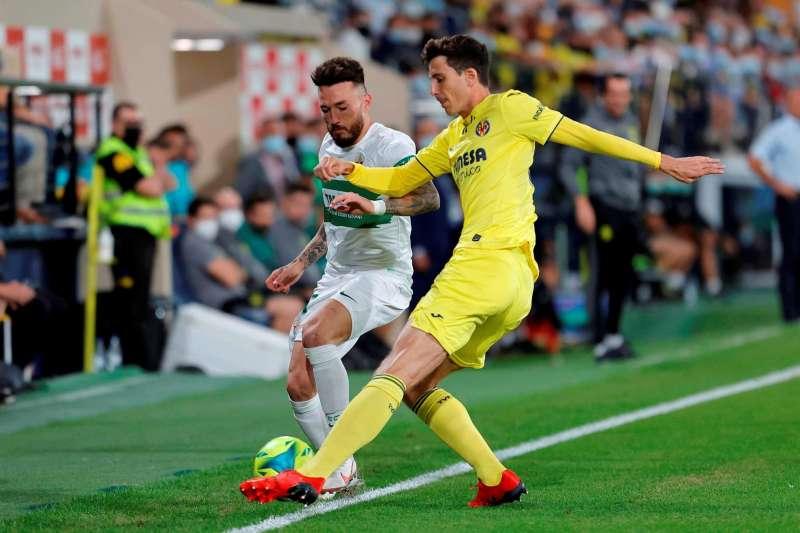 El defensa del Villarreal Pau Torres (d) pelea un balón con el centrocampista del Elche Josan.