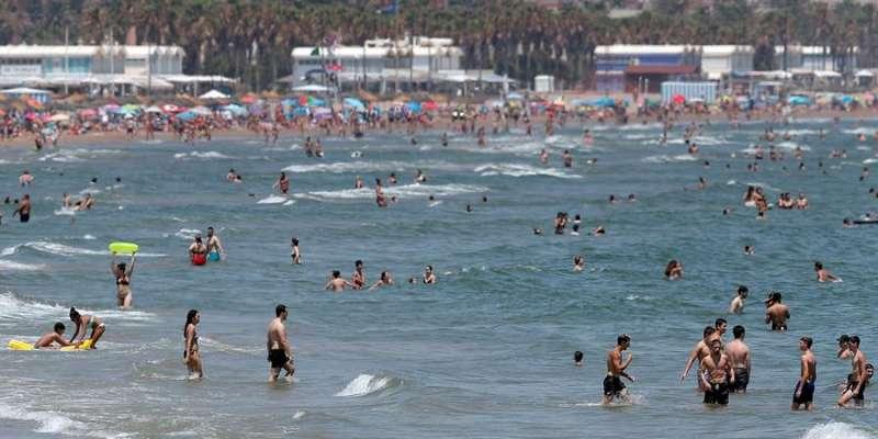 Un gran número de personas se refresca en las aguas de la playa de la Malvarrosa de València este primer día de julio. EFE