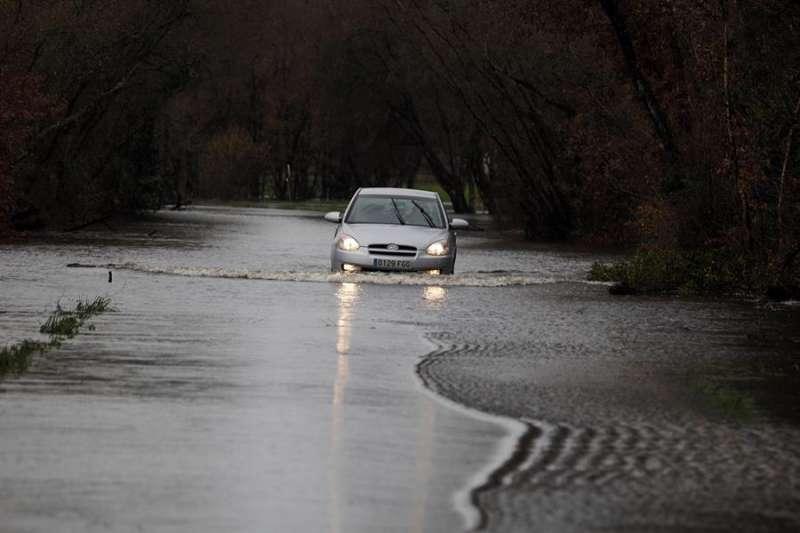 Un coche cruza una carretera anegada por las lluvias. . EFE/Archivo