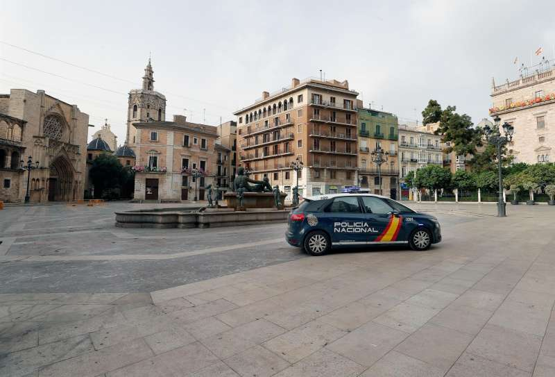 Un coche de la Policia Nacional vigila la Palza de la Virgen de Valencia.